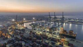 Aerial view timelapse unloading cargo on container ship in port at twilight Thailand.
