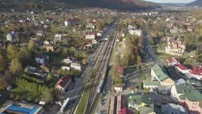 Aerial view to autumn carpathian city Yaremche at sunny day with train. Aerial view to autumn carpathian city Yaremche at sunny day with rail ways and train stock video