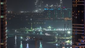 Aerial view to Dubai marina skyscrapers with construction site and Palm Jumeirah Island on background night timelapse. Building of new ship terminal stock footage