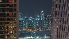 Aerial view to Dubai marina skyscrapers with construction site and Palm Jumeirah Island on background night timelapse. Building of new ship terminal stock video footage