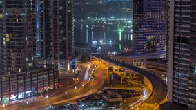 Aerial view to Dubai marina skyscrapers with construction site and Palm Jumeirah Island on background night timelapse. Traffic on a road and bridge stock video
