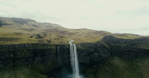 Aerial view to the mountains valley. The river flows through the hills and then falls down. Seljalandsfoss waterfall. stock video footage