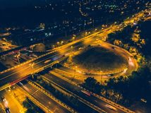 Aerial view to road junction with bridges and highways, modern city with night illumination and car traffic royalty free stock photo