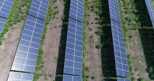 Aerial view to solar power plant. Industrial background on renewable resources theme. flying over rows of solar panels. Solar panels, solar panels on the field stock video footage