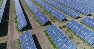 Aerial view to solar power plant. Industrial background on renewable resources theme. flying over rows of solar panels. Solar panels, solar panels on the field stock video