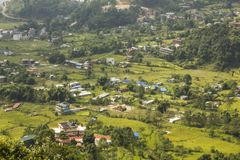 A aerial view to a village in a green mountain valley with rice fields. Aerial view to a village in a green mountain valley with rice fields royalty free stock images