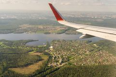 Aerial view to wing of an airplane over Moscow Region. Aerial view to the wing of an airplane over Moscow Region Royalty Free Stock Images