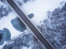 Aerial view or top view of bridge and frozen river in snow at winter landscape stock photo