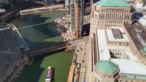 Aerial view of tour boat as it crosses the Chicago River alongside Merchandise Mart. Aerial view of tour boat as it crosses the Chicago River alongside busy stock footage