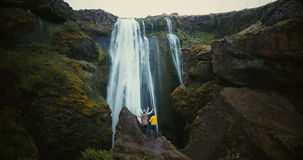 Aerial view of the tourist looking on Gljufrabui waterfall in Iceland. Group of people enjoying the scenic landscape. stock video footage
