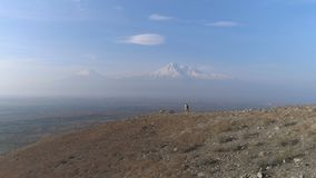 Aerial view: tourist man standing on the mountain. Aero shot: backpacking extreme expedition at Armenia. Aerovideo: unmanned aircraft flying above wonderful stock video footage