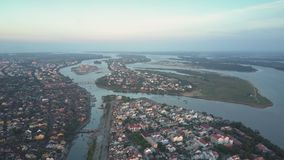 Aerial view town buildings surrounded by big blue calm river stock video footage