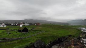 Aerial view of the town in the Faroe Islands, a territory of Denmark in the Atlantic Ocean. Church, cemetery and houses. With grass on the roof stock video