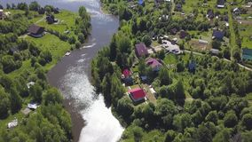 Aerial view of a town with many green trees located along the river in a sunny summer day. Clip. Ecologically clean area stock video