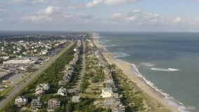 Aerial view of town, ocean and beach. 4k. Flying with drone near fancy house in Avon, NC, USA. Aerial footage of ocean, beach and city stock footage