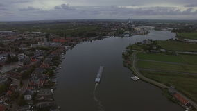 Aerial view of town and river with sailing ship, Netherlands stock video footage