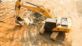 Aerial view of Tracked excavator starts digging ground preparing to build condominium. track hoe working. Site preparation stock photos