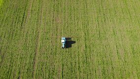 Aerial view tractor with fertilizer sprayer moves on field with green wheat or barley