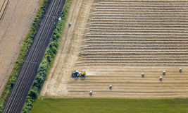 Aerial View : Tractor in a field  along a railroad. Aerial View : Tractor baling in a field along a railroad Royalty Free Stock Photo