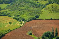 Aerial view of a tractor on field and  wooded hill Stock Photo