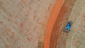 Aerial view of a tractor harrowing the soil to plant soybeans stock video footage