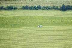 Aerial view of a tractor harvesting a green field. stock photo