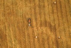 Aerial view of tractor making hay bale rolls in field Stock Image