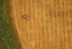 Aerial view of tractor making hay bale rolls in field Royalty Free Stock Photo