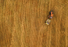 Aerial view of tractor making hay bale rolls in field Royalty Free Stock Photography