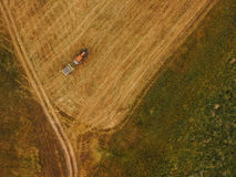 Aerial view of tractor making hay bale rolls in field Royalty Free Stock Image