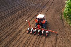 Aerial view of tractor with mounted seeder performing direct seeding. Of crops on plowed agricultural field. Farmer is using farming machinery for planting royalty free stock images