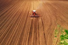 Aerial view of tractor with mounted seeder performing direct seeding. Of crops on plowed agricultural field. Farmer is using farming machinery for planting royalty free stock photos