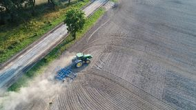 Aerial view on tractor ploughing field. Stock Photos