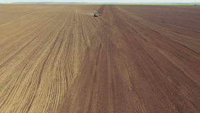 Aerial view of tractor plowing the soil on the field in sunny spring day stock footage