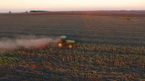 Aerial view of tractor plowing the soil on sunset stock video footage