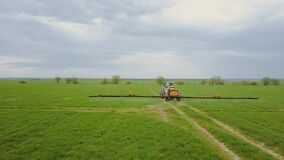 Aerial view of tractor spraying wheat field fly ower