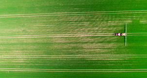 Aerial view of tractor spraying wheat field stock video footage