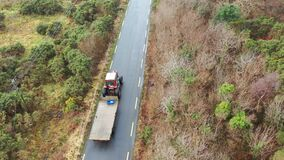 Aerial view of tractor and trailer driving on rural road in Ireland