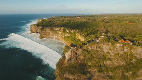 Rocky coastline on the island of Bali. Aerial view. Aerial view of Traditional Hindu temple Pura Uluwatu. Rocky coast with surf the waves off the at sunset stock footage