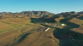 Aerial view of yurts between montains Mongolia. Aerial view of traditional yurts between montains at sunset, Mongolia, 4k stock footage