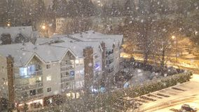 Aerial view of traffic flow and low rise apartment on cold blizzard snow winter. Night stock footage