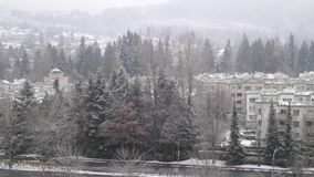 Aerial view of traffic flow and low rise apartment on cold blizzard snow. Winter day stock footage