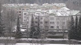 Aerial view of traffic flow and low rise apartment on cold blizzard snow. Winter day stock video