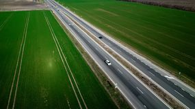 Aerial view of traffic on two lane road through countryside and cultivated fields stock images
