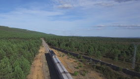 Aerial view of train in the country, heading forward. Train running forward over railway in the forest, heading forward, aerial view stock video