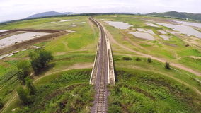 Aerial view train crossing bridge on dam,Beside a mountain forest and water resources,Thailand stock video