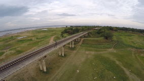 Aerial view of  train crossing bridge. Video shot from a drone show aerial view of  train crossing bridge in Thailand stock video footage