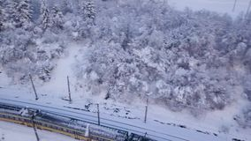 Aerial view of the train going through the mountainous terrain in winter. Carpathian Mountains, Ukraine stock video