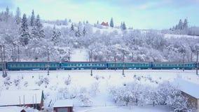 Aerial view of the train going through the mountainous terrain in winter. Carpathian Mountains, Ukraine stock footage