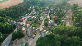 Aerial View of Train Going on The Old Bridge Viaduct in Green Wood Near The Village. Railroad Over Valley. stock video